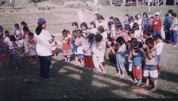 Children pray before an activity